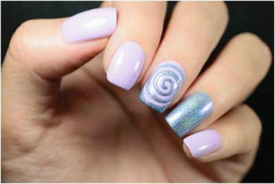 Winter holiday design made with trendy stylish silver and blue glitter on pink nail polish
