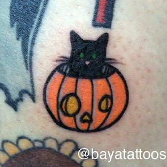 tiny black cat in pumpkin tattoo