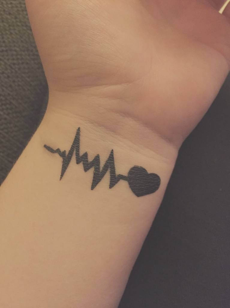 black ink heart beat tattoo with heart on wrist