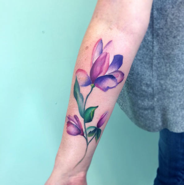watercolor flower tattoo design on forearm