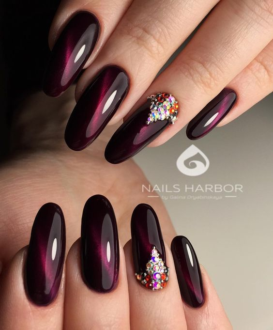 dark maroon nails with pearls on one finger
