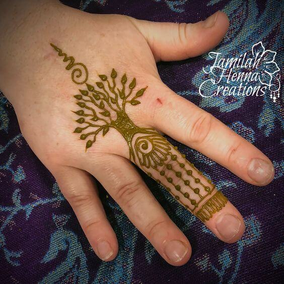 tree of life with unalome henna design on middle finger