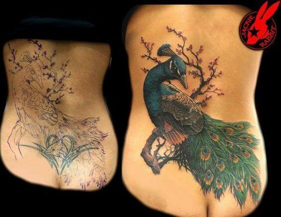 beautiful lower back peacock cover up tattoo design